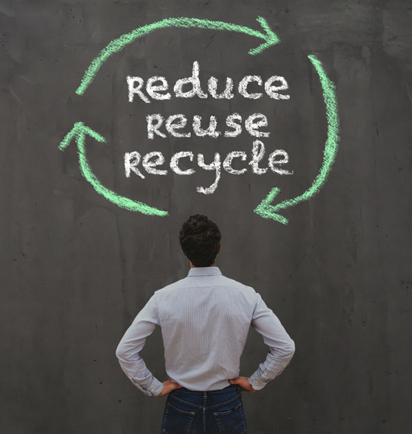 Man standing in front of wall with text reduce-reuse-recycle
