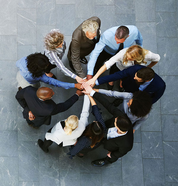People standing in a circle bringing hands together